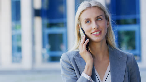 Cheerful-businesswoman-talking-on-phone-near-building