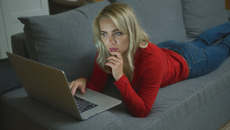 Serious-woman-with-laptop-lying-on-couch