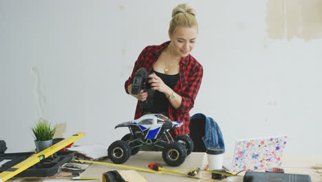 Woman-playing-with-radio-controlled-car-in-workshop
