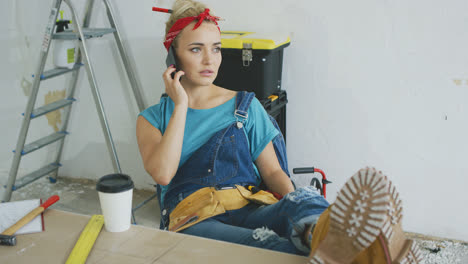 Worried-female-at-workbench-talking-on-smartphone-