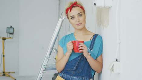 Smiling-female-in-overalls-leaning-on-wall-