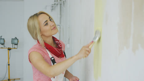 Smiling-woman-painting-wall-yellow