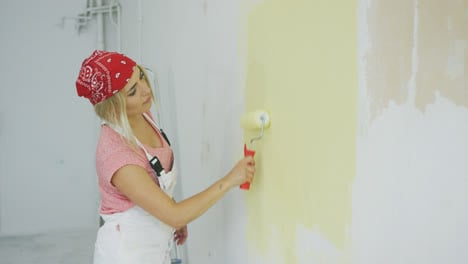 Woman-painting-wall-with-roller-