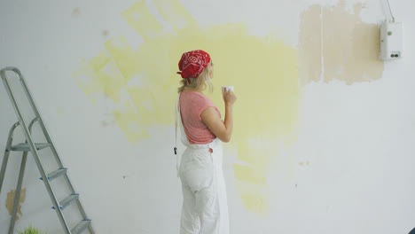 Female-painter-with-drink-looking-at-wall