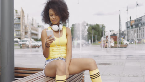 Sporty-girl-using-smartphone-on-bench