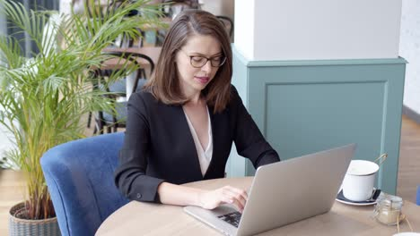 Happy-young-businesswoman-using-laptop-computer-in-a-cafe