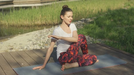 Young-woman-doing-yoga-twist-in-park
