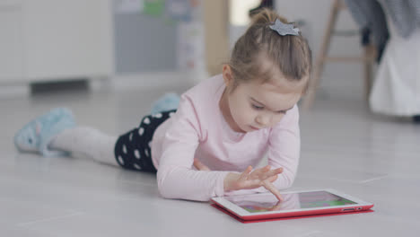 Relaxing-girl-playing-tablet-on-floor