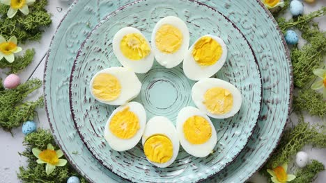 Easter-table-setting-with-flowers-and-eggs-Decorative-plates-with-boiled-eggs