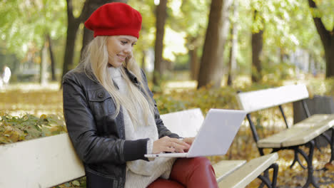 Woman-using-laptop-in-autumn-park