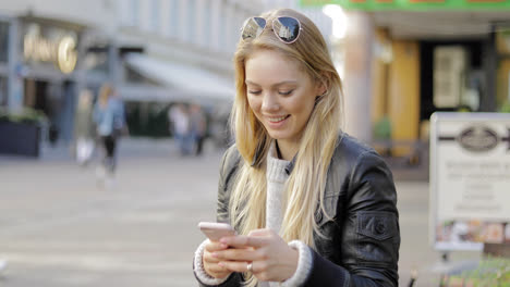 Smiling-woman-using-smartphone-on-street