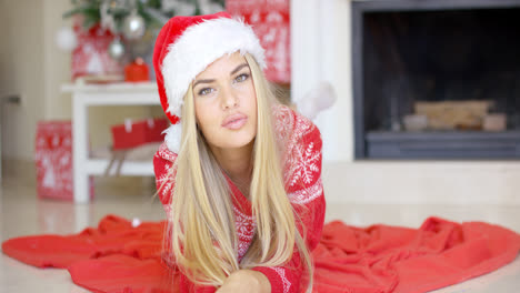 Young-happy-girl-lying-on-red-blanket-next-to-fireplace