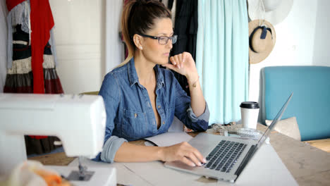 Pensive-female-with-laptop-working-