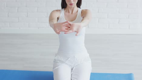 Beautiful-woman-stretching-arms-while-doing-yoga