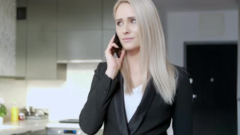 Smiling-blonde-middle-age-woman-managing-director-having-smartphone-conversation