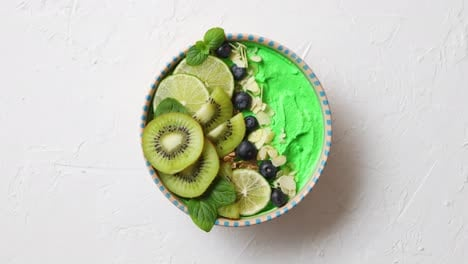 Green-smoothie-or-yogurt-bowl-With-fresh-kiwi-blueberries-lime-and-almond-flakes
