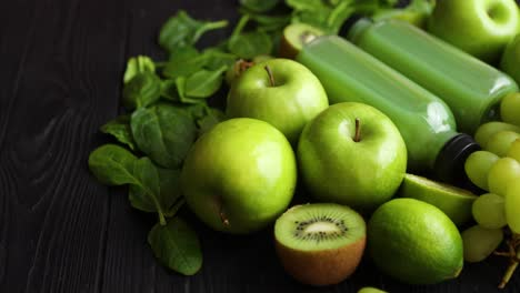 Mixed-green-fruits-and-vegetables-placed-on-black-wooden-table