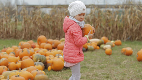 Girl-playing-with-pumpkins-in-garden