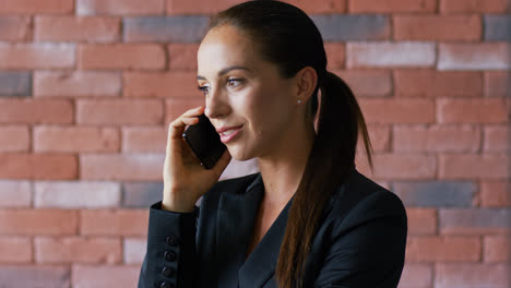 Businesswoman-with-ponytail-having-phone-conversation