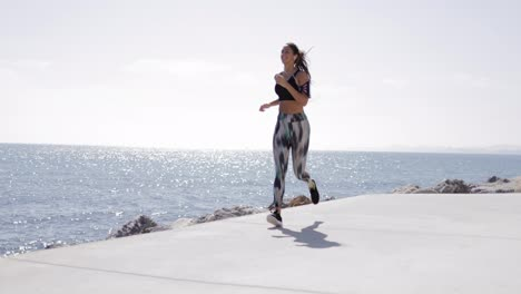 View-of-fit-girl-in-sportswear-running-along-seafront