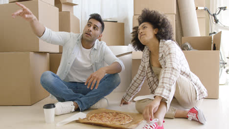 Young-couple-eating-pizza-and-chatting