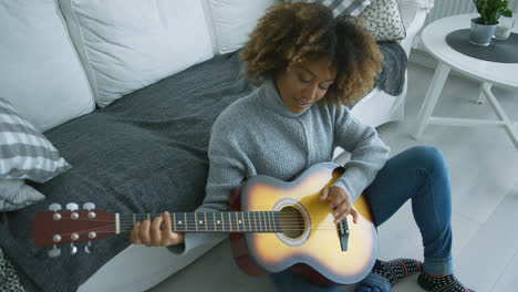 Relaxed-woman-playing-guitar-at-home