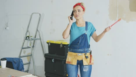 Doing-home-repairs-woman-talking-on-smartphone-