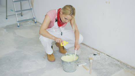 Woman-mixing-wall-paint-in-bucket-
