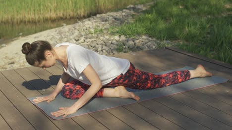 Young-woman-doing-yoga-exercises-on-mat-in-summer-day