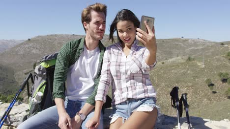Smiling-couple-taking-selfie-in-mountains