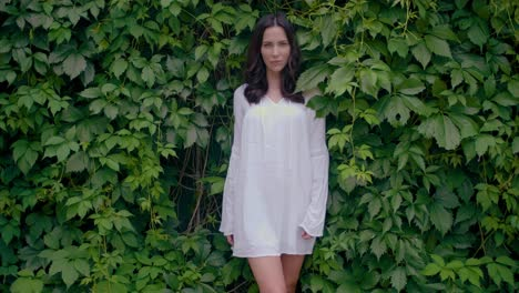 Female-model-in-white-tunic-dress-with-green-leaves-on-background