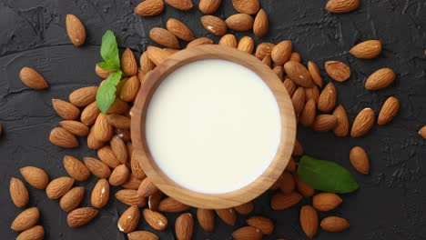 Fresh-almond-milk-in-wooden-bowl-and-almonds-on-black-stone-background