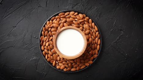 Composition-of-almonds-seeds-and-milk--placed-on-black-stone-background-