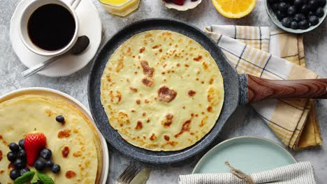 Delicious-pancakes-on-stone-frying-pan-Placed-on-table-with-various-ingredients