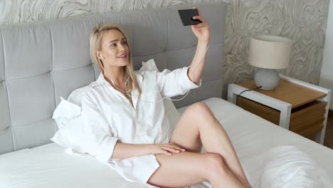 Beautiful-smiling-middle-aged-woman-making-selfie-in-bedroom