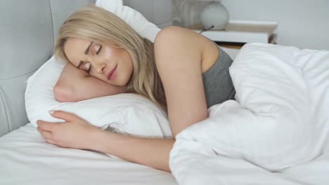 Young-beautiful-blonde-woman-sleeping-in-her-bedroom
