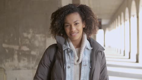 Portrait-of-young-beautiful-mixed-race-woman-with-afro-haircut-walking
