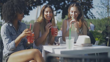 Stylish-young-girls-having-drinks-outside