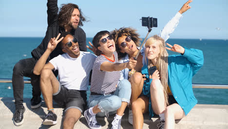 Happy-friends-posing-for-selfie-on-seafront