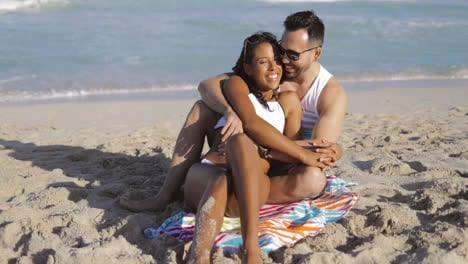 Cuddling-happy-couple-on-beach