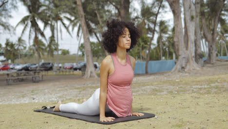 Confident-black-woman-stretching-on-mat