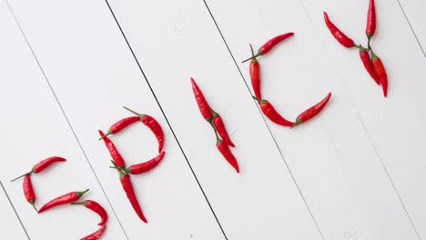 A-word-SPICY-formed-with-small-red-chilli-peppers-Placed-on-white-wooden-table