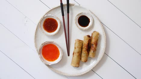 Fried-Chinese-Thai-or-Vietnamese-traditional-spring-rolls-or-nems-served-on-ceramic-plate