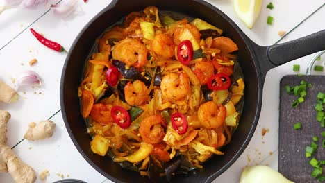 Fresh-fried-noodles-with-vegetables-with-shrimps-served-in-black-iron-pan-With-various-ingredients