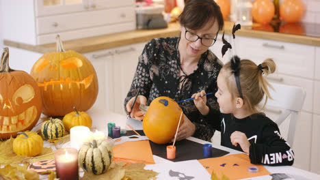 Mother-and-daughter-painting-face-on-pumpkin