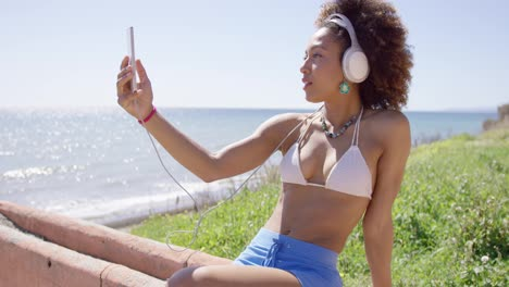 Female-wearing-swimsuit-top-and-blue-shorts-taking-selfie