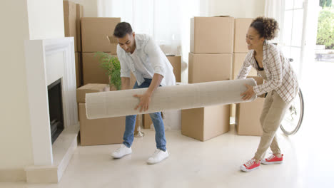 Young-couple-carrying-a-rolled-rug-into-a-house