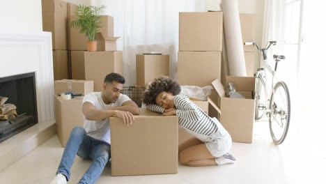 Tired-young-couple-relaxing-on-cardboard-boxes