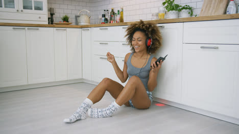 Laughing-woman-with-gadgets-in-kitchen