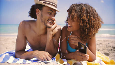 Couple-on-beach-listening-to-music-and-smiling